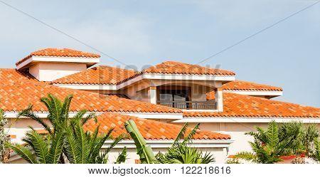 Orange Clay Tiles Under Blue Skies Beyond Green Palm Trees