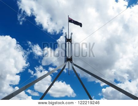 Canberra, Australia - January 28, 2015: The Australian flag flying on top of Parliament House with clouds and blue sky