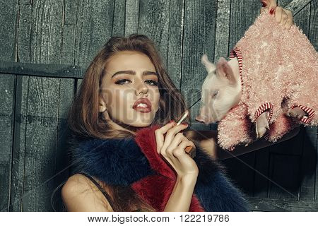 Beautiful young sensual woman holding cute pink small pig pet in cloth