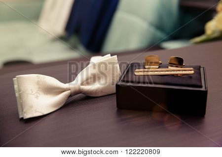 cufflinks and a white bow tie on the table