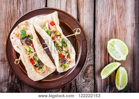 homemade tacos with salmon, onion, cucumber and avocado