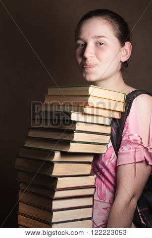 cute and young girl in the hands of a lot of books