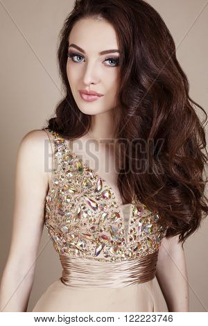 fashion studio photo of gorgeous young woman with dark hair and evening makeup, wears luxurious dress