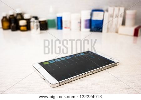 Tablet pc on white table  with medical objects on background as an image for electronic diagnostic or healthcare mobile apps. Medical background