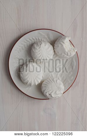 Marshmallow or vanilla zephyr on white dish on a light wooden background. View from top. One piece of marshmallow is bitten. Zephyr - export commodity of Latvia.