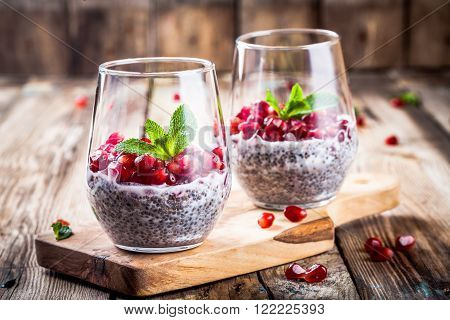 chia pudding with pomegranate seeds and mint on rustic wooden table