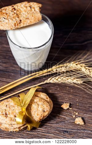 Chip cookies and glass of milk on wooden background
