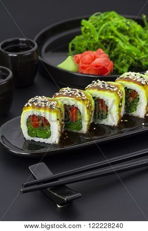 Vegetarian Sushi Roll With Avocado Ginger Wasabi And Chuka Salad Over Black Background