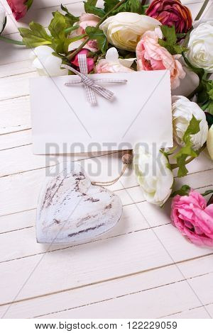 Flowers in pink colors with decorative heart and empty tag on white wooden background. Selective focus is on tag. Place for text.