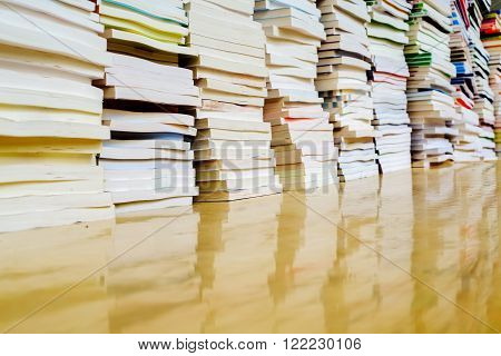 Placed neatly stacked rows of books on the desk