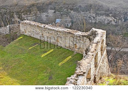 Fragment of ancient walls of the medieval fortress above the canyon in Kamianets-Podilskyi, Ukraine, early spring, view from above