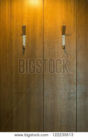 Two Steel Wall Hangers Wall Hooks for coats on wooden board background.