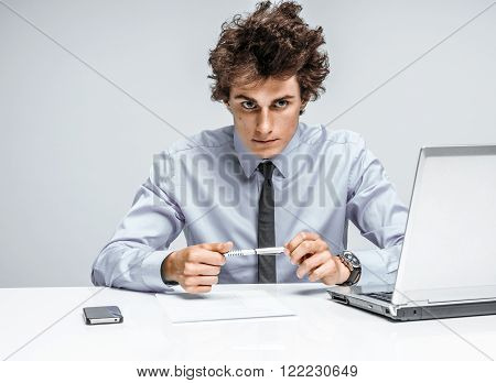 Ambitious young businessman looking at camera with serious look / businessman at the workplace working, depression and crisis concept