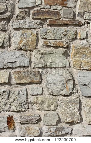 Wall of large rough granite boulders fortified by cement, vertical photo