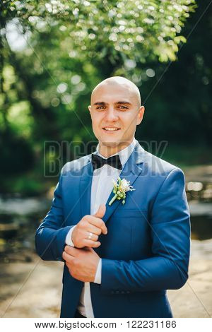 Groom in a blue suit buttoning cuffs in park