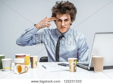 Young businessman with gun wants to commit suicide / modern office man at working place, depression and crisis concept