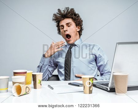 Sleepy exhausted young manager in yawn. Modern businessman at the workplace working with computer depression and crisis concept