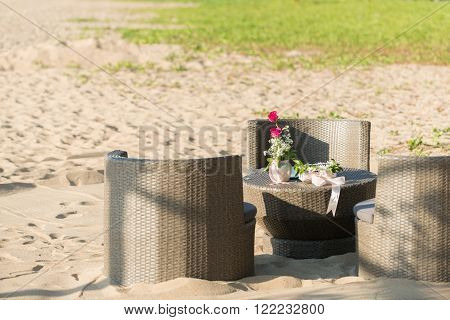 relaxing table setup on the beachside white sand and green leafs background.