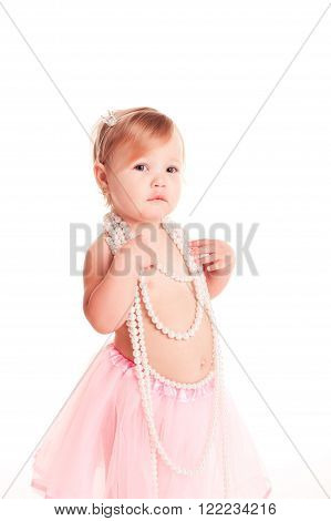Cute baby girl 1-2 year old wearing pearl necklace over white. Looking at camera. Childhood.