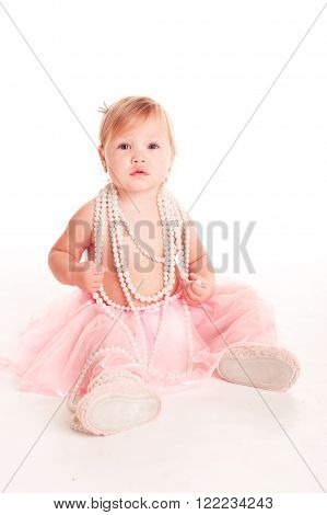 Cute baby girl 1-2 year old wearing pink fluffy skirt and pearl necklace over white. Looking at camera. Childhood.
