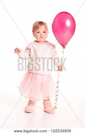 Cute baby girl 1-2 year old holding pink balloon over white. Isolated. Looking at camera. Playful. Childhood.