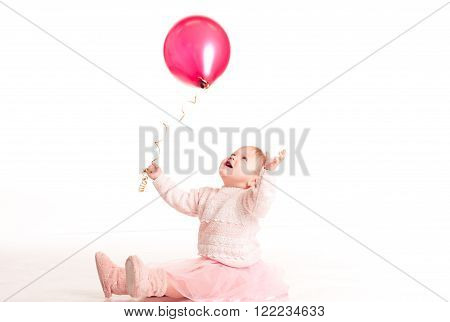 Happy baby girl 1-2 year old playing with pink balloon in room over white. Isolated. Happiness.