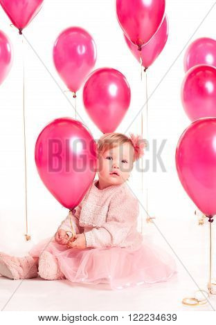 Cute baby girl 1-2 year old sitting on floor with pink balloons in room over white. Isolated. Birthday party. Celebration.