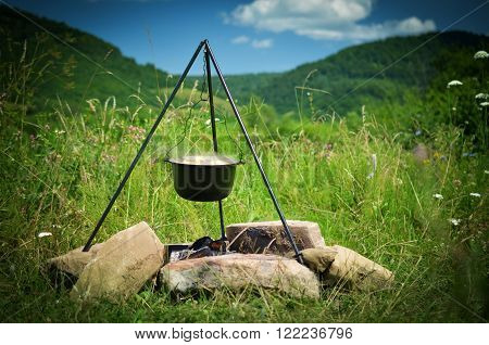 Tourist pot hanging over the fire on a tripod. Mountain landscape.