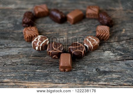 Different types of chocolate candies on a wooden background