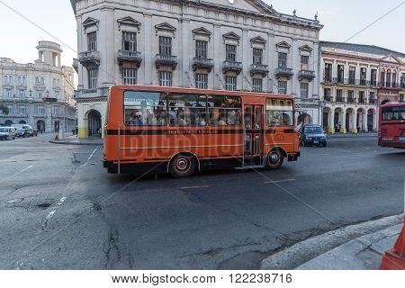 HAVANA, CUBA - APRIL 2, 2012: Orange school bus in front of Capitolio
