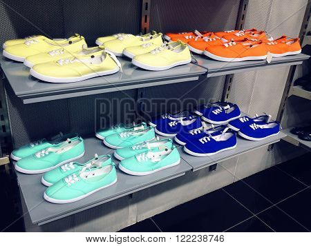 Colorful casual gumshoes on shelf in fashion store