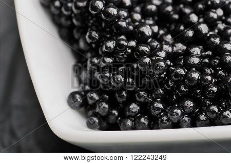 black caviar in the white ceramic bowl close-up on the dark background horizontal