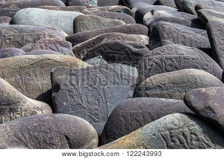 Carved Buddhist Mani Stones near Thiksay Monastery, Leh, Ladakh. Mani stones are rocks inscribed with the six syllabled mantra of Avalokiteshvara, as a form of prayer in Tibetan Buddhism.