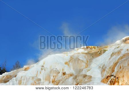 Steam escapes from Mammoth Hot Springs in Yellowstone National Park. Blue sky frames white and orange limestone mounds of Upper Terrace.