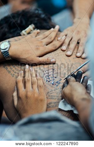 BANGKOK, THAILAND - MARCH 23, 2013: Master makes traditional Yantra tattoo on magic tattoo Sak Yant holiday at Wat Bang Phra, Thailand