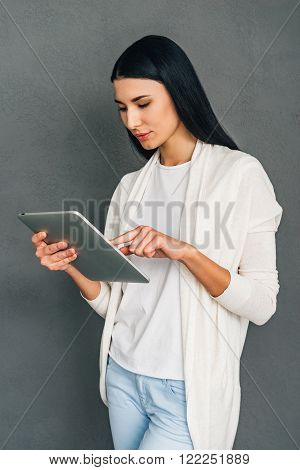Enjoying her new touchpad. Beautiful young woman using her digital tablet while standing against grey background