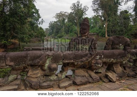 Statues Of Ancient Khmer Warrior Heads Carry Giant Snake Decorating Bridge To Bayon At Angkor Wat Co