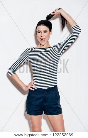 Crazy and stylish. Beautiful young woman pulling her ponytail and keeping mouth open while standing against white background