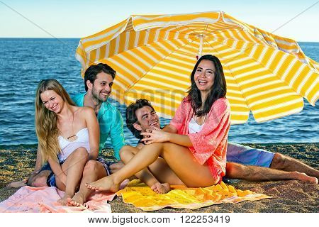 Two young couples on a beach under an umbrella. Two young smiling couples seated on sandy beach near the ocean under a large striped yellow umbrella.