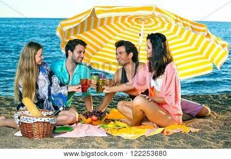 Two couples toast under an umbrella on the beach, having a picnic.