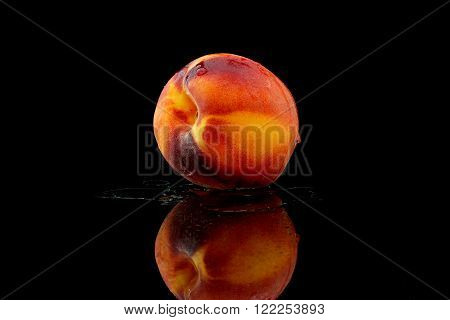 a peach with water on black background