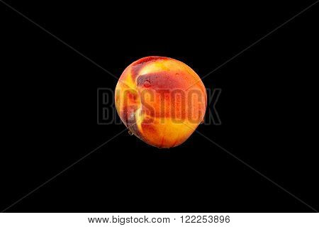 a peach with drops of water on black background