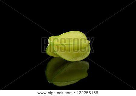 One is reflecting starfruit on black background
