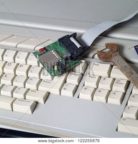 Rusty wrench laid across a retro looking outdated computer keyboard concept of computer service and repair