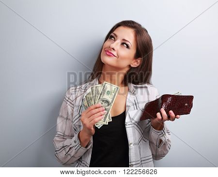Thinking Happy Woman Holding Dollars And Wallet In Hands And Want To Spend Money