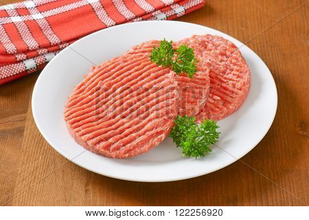 plate of raw hamburger patties on wooden table