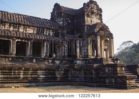 Angkor Wat, Siem Reap, Cambodia - Februaty 10, 2015 :: Asian girl seats on the ruins of Angkor Wat, Siem Reap Cambodia