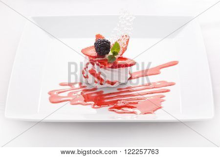 On a white porcelain cake plate. Dessert marshmallow meringue, mousse, cream, decorated with berries, caramel, mint and jam close-up isolated on white background.