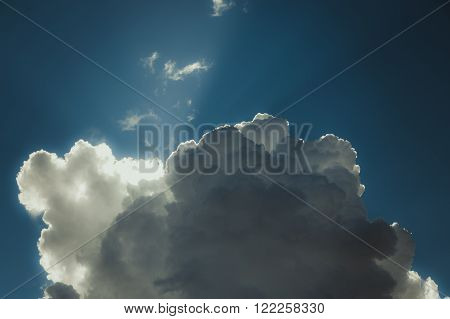 Sun rays shining through cumulonimbus clouds toning image