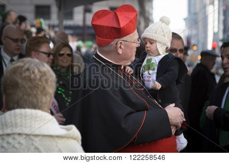 NEW YORK - MARCH 17, 2016: Timothy Cardinal Dolan Archbishop of New York talks to a small child in front of St Patricks Cathedral on Saint Patricks Day in Manhattan on March 17, 2016.